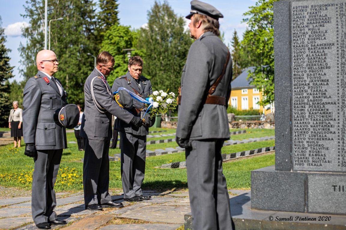 Kuvassa kolme sotilasasta laskemassa kukkalaitetta Lapuan sankarihautasmaalla 1939-1944 sodissa kaatuneiden muistomerkille.