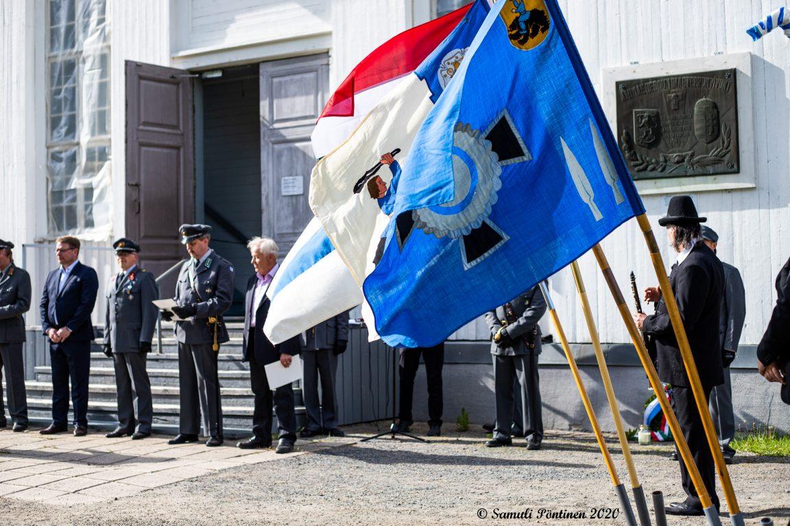 Kuvassa etualalla Lapuan reserviläisten lippu ja sen takana muita lippuja. Taaempana kirkon portaiden edessä seisomassa ihmisiä, joista osa on sotilasasuissa.