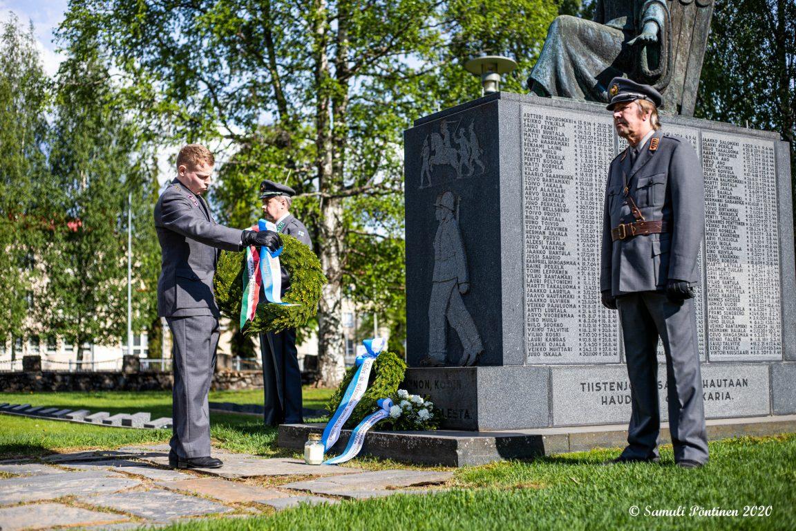 Kuvassa sotilas on laskemassa seppelettä muistomerkille, ja kaksi sotilasta on muistomerkin edessä kunniavartiossa.